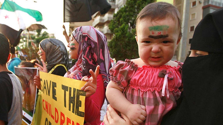 A child with a Syrian opposition flag painted on the face takes part in a protest in Tripoli, northern Lebanon, against an attack by Syrian President Bashar al-Assad's forces on the Syrian city of Houla.