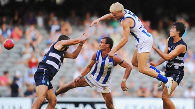 North Melbourne's Ben Warren flies over teammate Corey Jones and Cats Josh Hunt (left) and Andrew Mackie.