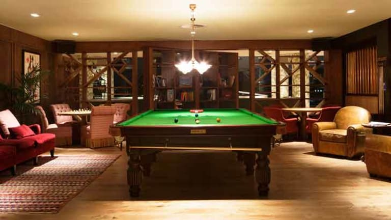 The Reading Room at The Stables features a pool table, low seating areas, chess tabletops and a large, rotating bookshelf which leads through to the Music Room.