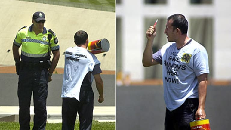 Marat Aminov threatens to set himself on fire outside Parliament House yesterday, as captured by the Canberra Times.