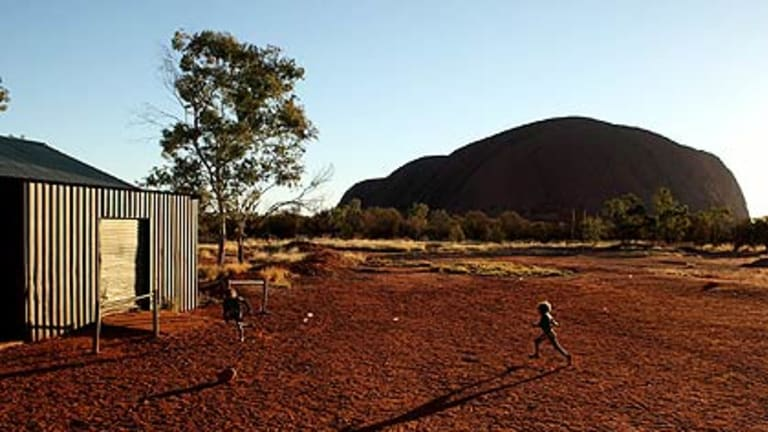 Long shadows of intervention   ...  youngsters at play in the shadow of Uluru near the settlement of Mutitjulu.