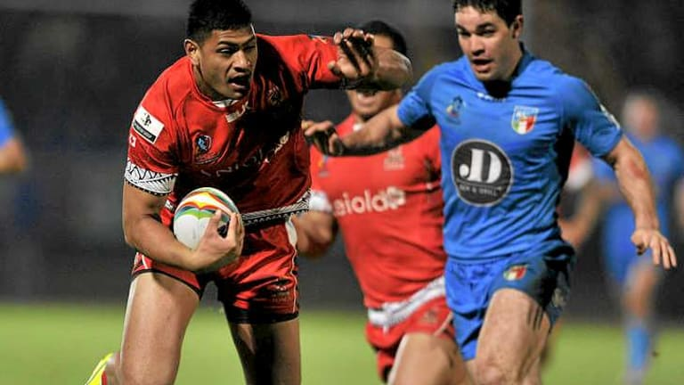 Tonga winger Daniel Tupou is tackled by his Roosters' NRL teammates Anthony Minichiello (unseen) and Aiden Guerra.