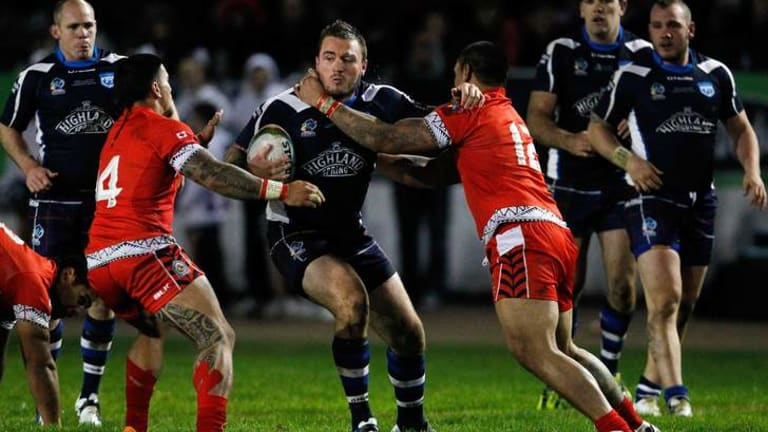 Brett Phillips (C) of Scotland is tackled by Nafe Seluini (L) and Sika Manu of Tonga.