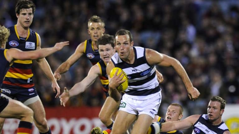 Cunning Cat: Brad Ottens evades the outstretched arms of a flock of Crows in Geelong's tough encounter at AAMI Stadium last night.