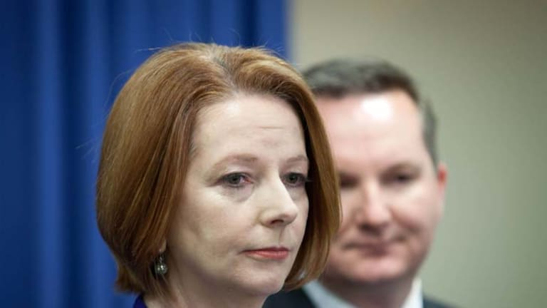 Hammered ... Julia Gillard and Chris Bowen, the Minister for Immigration, at a news conference in Brisbane yesterday.