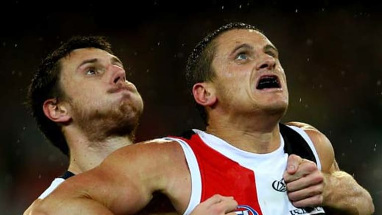 Mark Blake of the Cats contests a boundary throw-in with Michael Gardiner of the Saints.