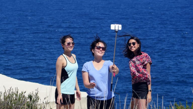 Three women pose for a group selfie in front of Wedding Cake Rock in Bundeena.