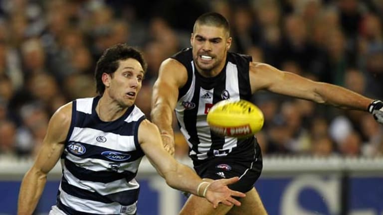 Harry Taylor leads Magpies forward Chris Dawes to the ball in round nine.