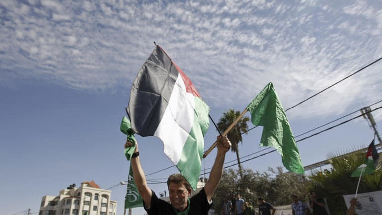 Nael Barghouti waves a green Islamic flag and a Palestinian flag to the crowd after arriving in Ramallah.