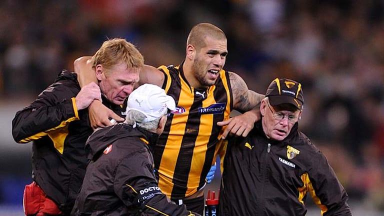 Hawk horror: Lance Franklin is helped off the MCG last night.