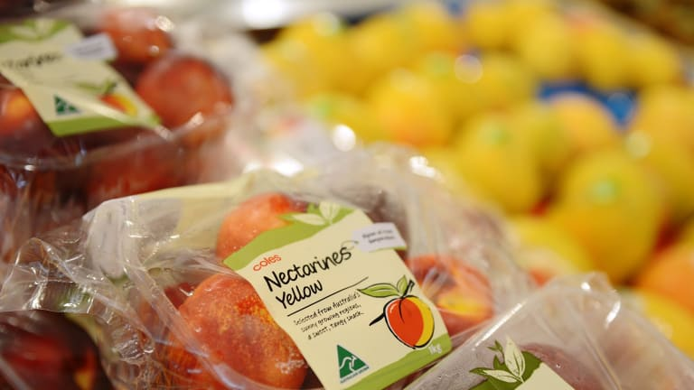 Store brand packages of nectarines are displayed for sale in the produce section.