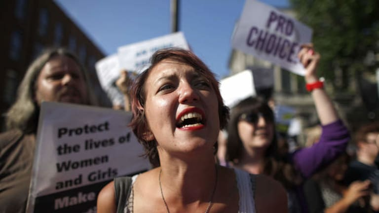 A Pro-Choice supporter holds placards in front of the gates of the Irish Parliament building in Dublin.