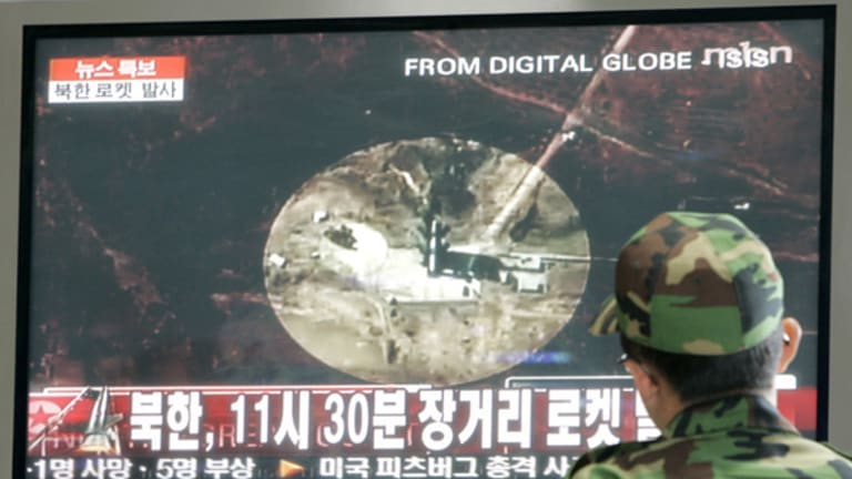 A South Korean Army soldier watches a TV news reporting a rocket launched by North Korea at a train station in Seoul.