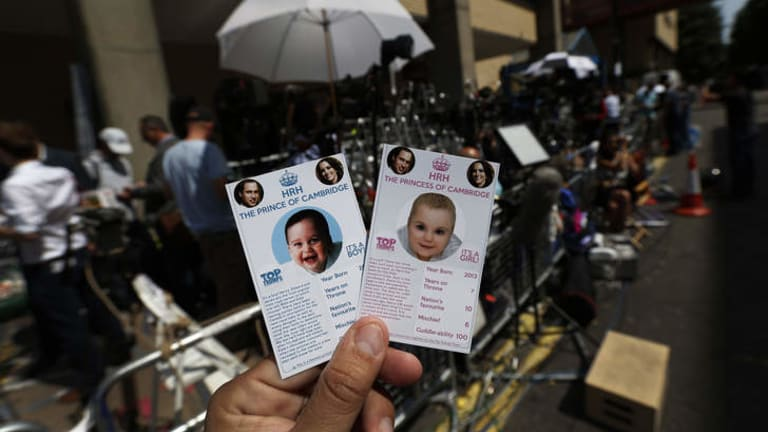 Cards depicting the 'royal baby', either as a boy or a girl, specially made by a games company as a publicity stunt are pictured, backdropped by members of the media waiting across the St. Mary's Hospital exclusive Lindo Wing in London.