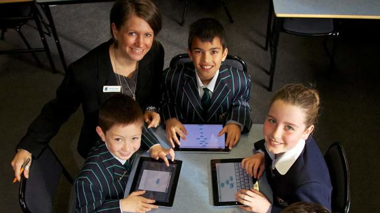 Pads out: Teacher Kate Hughes and her year 4 students at St Leonard's College, Brighton East. The school has embraced e-learning, using iPads in class with a student code of conduct in place after a six-month trial last year.