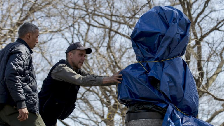New York City Parks workers remove a moulded bust of Snowden that was erected by a group of anonymous artists in 2015.