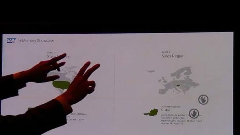 A man uses both hands to change screens and demonstrate SAP's HANA in a video demonstration. He can highlight regions on a map and call for results with gestures, using Kinect.