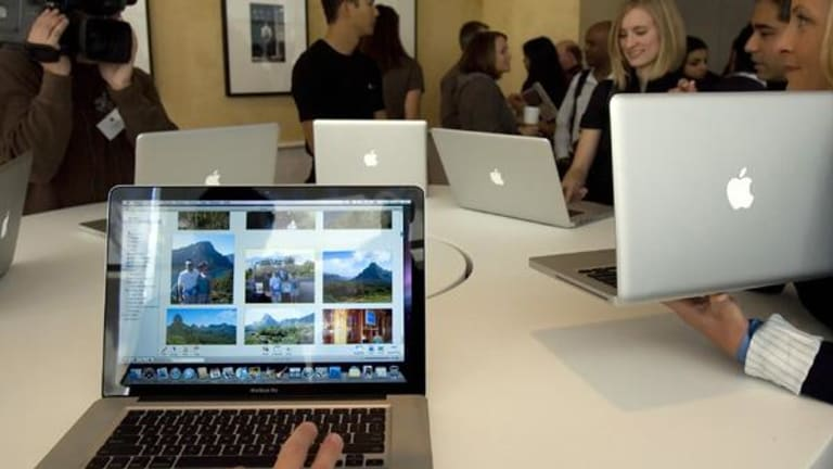 Journalists look at the new MacBook Pro notebook computers.