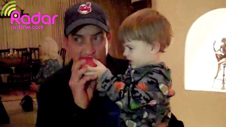 Charlie Sheen takes a bite from an apple while holding one of his 23-month-old twins before they are removed from his Hollywood Hills home.