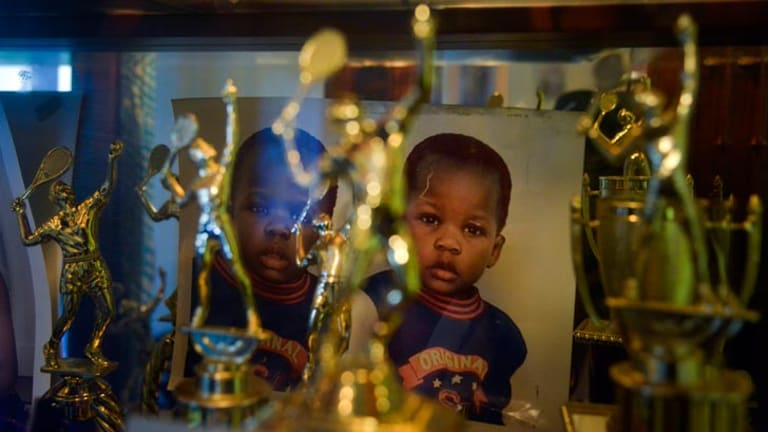 Photographs taken when Franklin and Francis Tiafoe were toddlers sit at the back of a cabinet filled with trophies in their apartment.