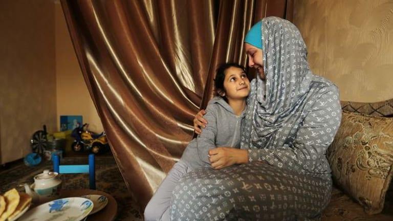 Tatar woman Zulfere Memetova embraces her daughter Adele, aged 8.