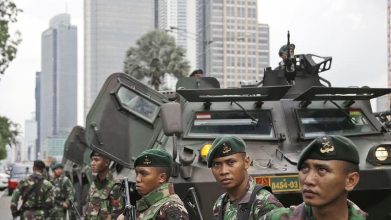 Indonesian soldiers stand guard in Central Jakarta, Indonesia on Thursday.