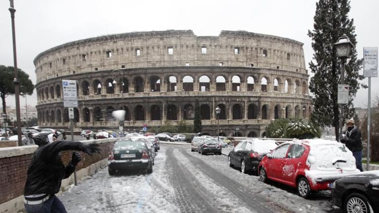 Boys throw snowballs in front of the Colosseum in Rome.