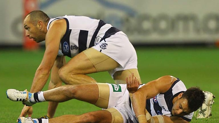 Concussed: Geelong's Jimmy Bartel struggles to get up after colliding with teammate James Podsiadly.