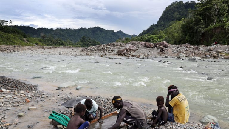 A family panning gold in the polluted Jaba river flowing from Panguna copper mine.