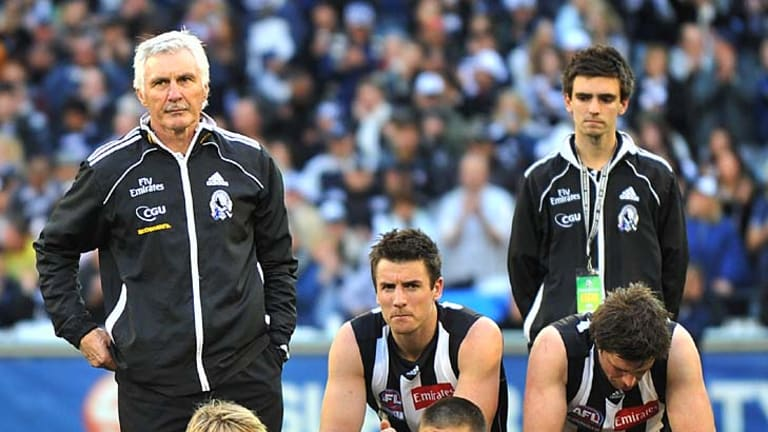 The fallen: coach Mick Malthouse (left) stands beside his players after the loss yesterday.