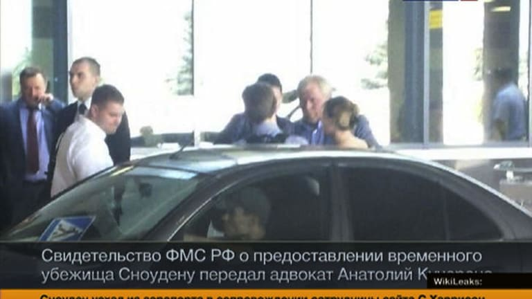 Russian lawyer Anatoly Kucherena, second right in the centre, and Edward Snowden, centre back to a camera, as Snowden leaves Sheremetyevo airport outside Moscow, Russia.