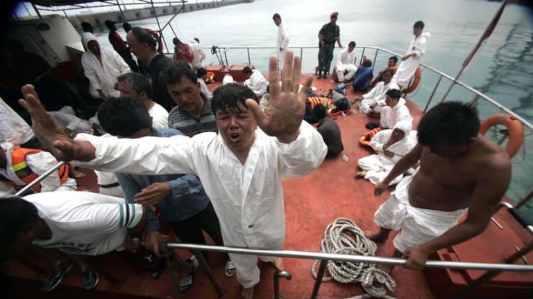 Survivors from the asylum boat at Merak port.