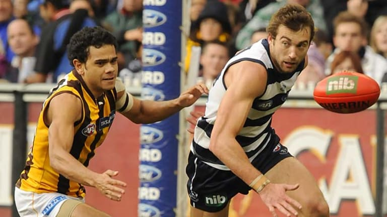 Neck and neck. Geelong's Corey Enright and Hawthorn's Cyril Rioli.