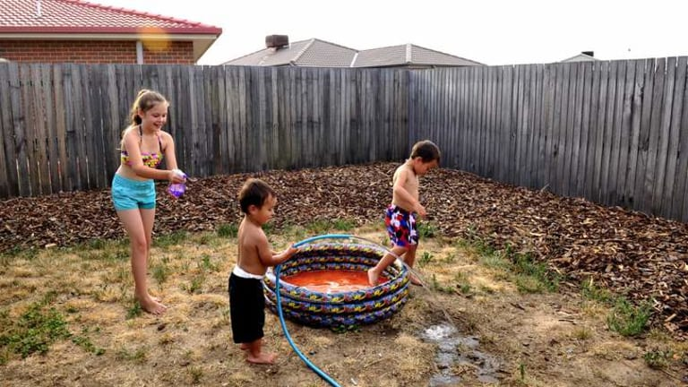 Studies have shown that the suburb of Macgregor was up to 7 degrees hotter than certain southside suburbs. L-R Aideen Fitzgerlad,9,  cools off with Nate Fitzgerald,2,  and Seth Fitzgerald,5  in their backyard in Macgregor.