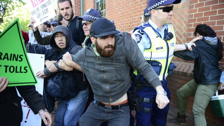 Clash ... Police grab east-west link protesters outside the Collingwood offices.