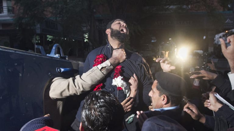 Malik Mumtaz Hussain Qadri, the bodyguard arrested for the killing of Punjab Governor Salman Taseer, shouts religious slogans while being taken away by police after he was presented at a court in Islamabad.
