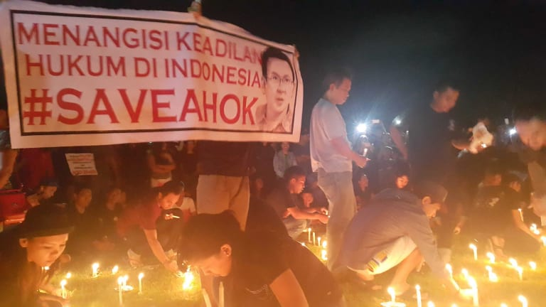 """Supporters conduct a candlelit vigil in Bali in support of Ahok. The sign reads """"Bitter over the lack of justice in Indonesian law""""."""