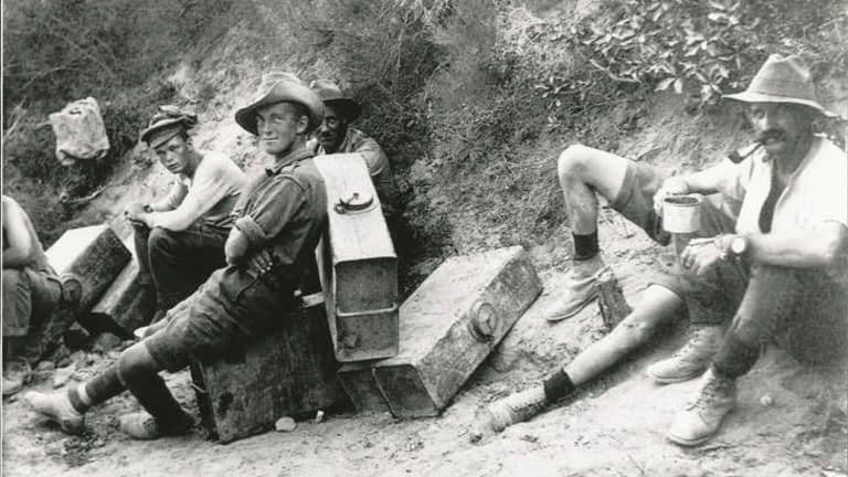 Men of the 6th Field Battery on water-carrying fatigues stop for a rest and a smoke. From <i>Anzac & Empire</i>.