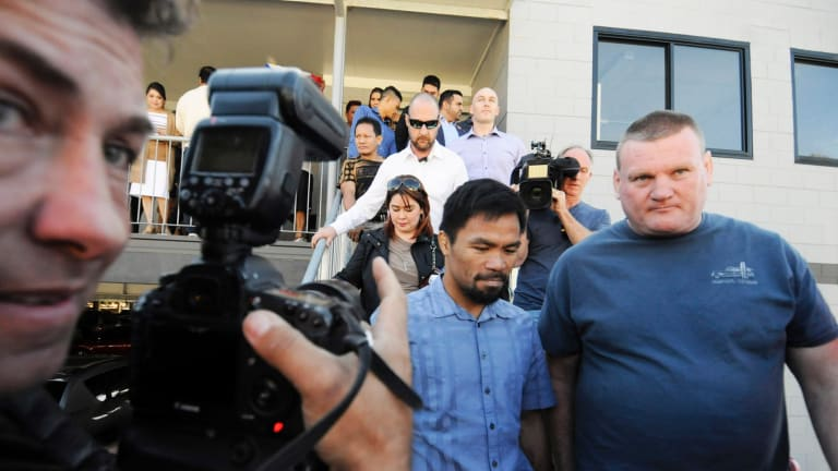 Manny Pacquiao with promoter Deano Lonergan (right) leave a church in Carina at the weekend.