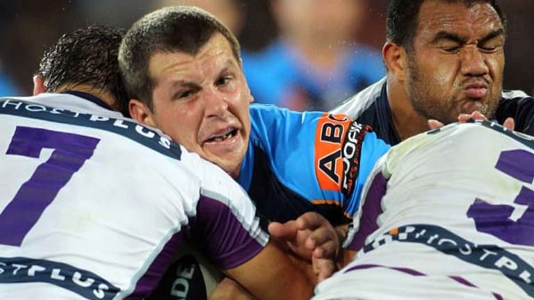 Greg Bird of the Titans runs into a wall of Storm defenders.
