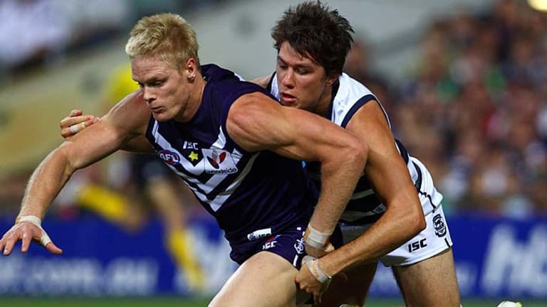 Adam McPhee of the Dockers and Andrew Mackie of the Cats contest the ball.