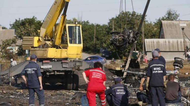Members of the Ukrainian Emergencies Ministry and medical personnel at the crash site of Malaysia Airlines flight MH17.