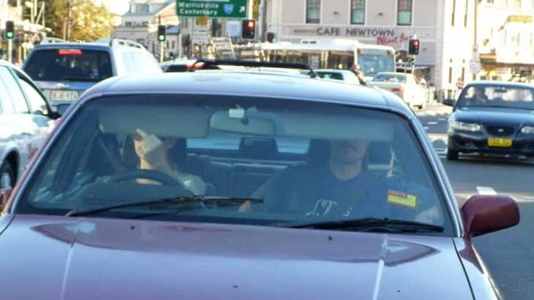 """The bird, a battery and a belt ... the couple in the car with the cardboard """"TRAFFIC"""" plate in Newtown."""