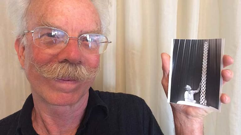 Artist Jon Barlow Hudson holds a photo of himself with a model of the sculpture.
