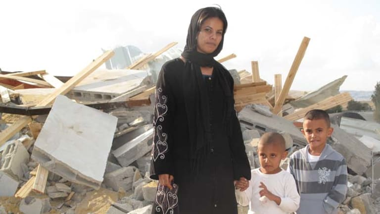 Demolished ... Rifa al-Oqbi and her sons Omar, 4, and Ali, 5, stand amid the ruins of their home, demolished by Israeli authorities, in the village of al-Qrain.