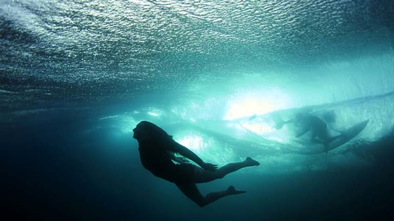 Into the wild ... surfer Taylor Miller dives beneath a wave while a surfer glides above the surface.