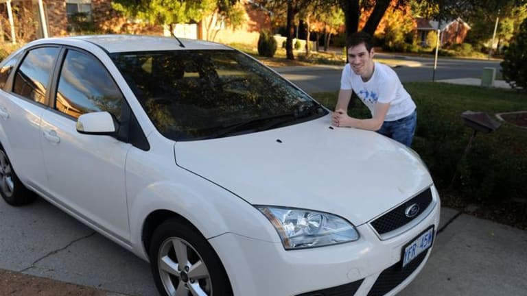 White car owner Blake Fenwick with his white Ford Focus, the most popular colour for cars in the ACT.