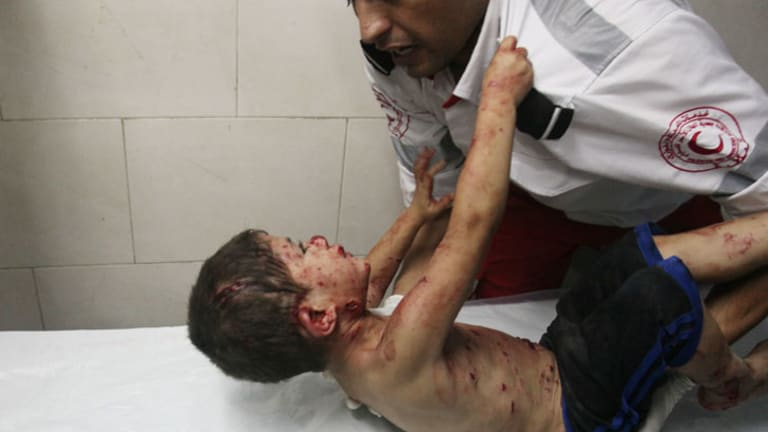 """The Palestinian boy, who was caught in artillery fire from Israel, screams at the paramedic: """"I want my father, bring me my father!"""""""