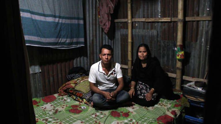 Forhad Mia and his wife Raifa sit in their slum bedsit in the Bangladeshi capital Dhaka.