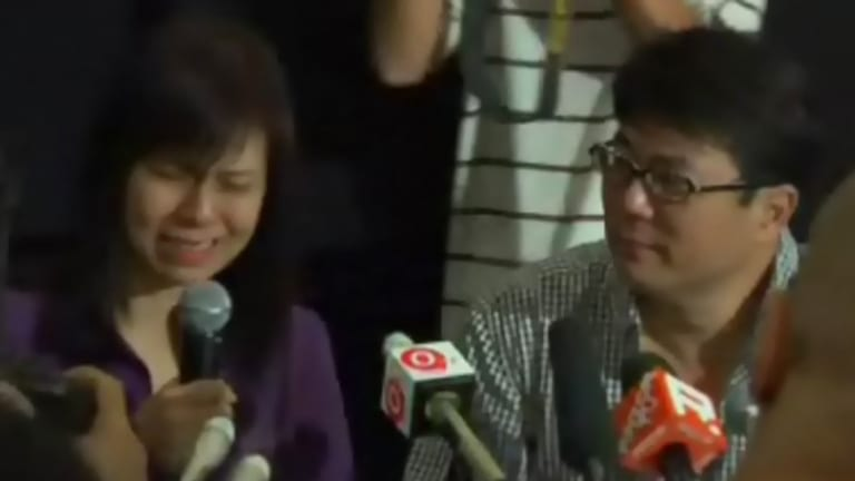 Singapore's Tiger Woods ... Jack Neo, right, looks on as his wife breaks down in tears while speaking to the media.
